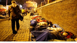 Faithful lie in sleeping bags as they stay overnight near the Vatican in Rome.