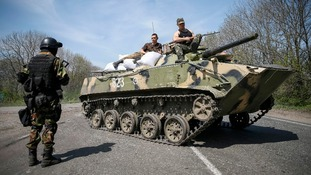 Ukrainian soldiers sit on top of an armoured personnel carrier at a checkpoint outside the city of Slaviansk today.