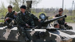 Ukrainian soldiers sit on top of an armoured personnel carrier