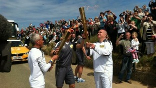 And the Olympic flame is passed on