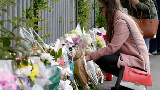 Flowers are left outside Corpus Christi Catholic College in Leeds following the much-loved teacher's death.