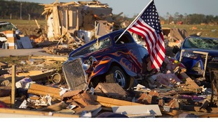 A US flag sticks out the window of a damaged hot rod car near near Vilonia, Arkansas.
