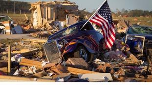 A US flag sticks out the window of a damaged hot rod car near near Vilonia, Arkansas.