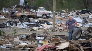 A worker at Mayflower RV retrieves wheels from a trailer destroyed in Mayflower, Arkansas.