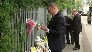 Mr Mort looking at tributes left outside the school