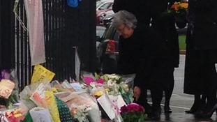 Ann Maguire's husband Donald lays a floral tribute by the railings of Corpus Christi Catholic College in Leeds.