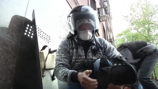 A pro-Russian demonstrator puts on riot gear stolen from authorities.