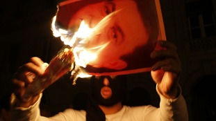 A protester burns a picture of Egypt's President Hosni Mubarak during clashes in Cairo January 28, 2011