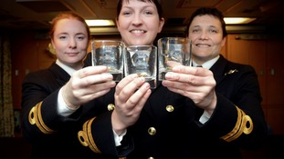 Three women in uniform smiling to camera, with glasses in their hands