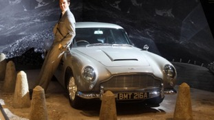 A waxwork of Sir Sean Connery posing with an Aston martin DB5 from the film Goldfinger