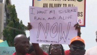 "A banner reads ""I want my sisters back and alive now""."
