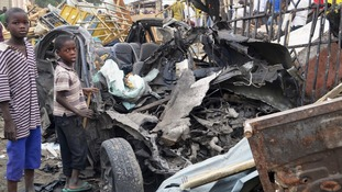Two boys stand near the charred chassis of a vehicle after a bomb attack in Maidugur.