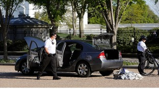 Members of the Uniformed Division of the Secret Service search the car near the White House.