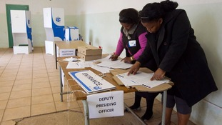 Election officials work in a classroom that has been transformed into a voting station in Embo.