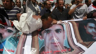 A man kisses a picture of a man who died during Egypt's revolutions after a court sentenced Mubarak to life in prison