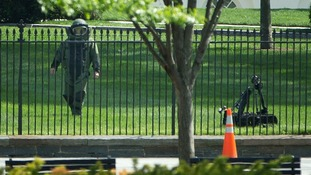 A bomb technician works with an explosives ordinance disposal robot to help recover an item thrown over the White House fence.
