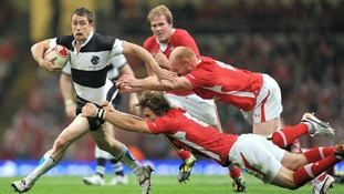 Wales' Liam and Martyn Williams tackle the Barbarians' Shane Williams