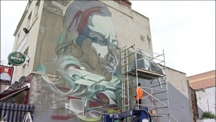 graffiti artist painting the side of a building
