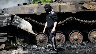 A masked pro-Russian walks past an armoured personnel carrier after the clashes