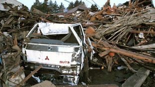 A truck and destroyed buildings swept by a tsunami following Japan's earthquake last year