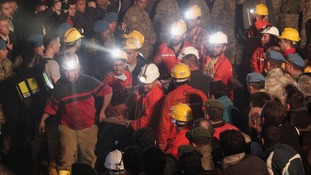 The body of miner is carried to an ambulance in Soma after an explosion in the mine