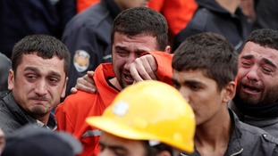 Relatives of miners who were killed or injured in a mine explosion react as rescuers continue their work