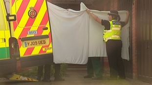 Police hold up sheets as two patients were taken out of the house