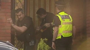 Officers use a battering ram to gain entry to the house