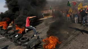 A man jumps over burning tyres at protests in Brazil.