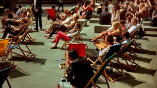 People sun themselves in deckchairs at Regent's Square in London.