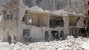 Residents inspect the damage in a destroyed neighbourhood in Aleppo on 18 May