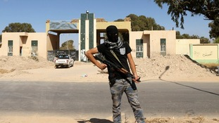 A militia stands guard in front of the entrance to a militia camp in Benghazi on 16 May