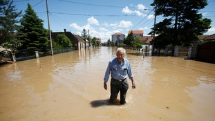 A man walks through flood water in the town of Obrenovac in Serbia