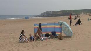 A family enjoys the sunshine on Sandhaven beach.