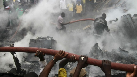 People help rescue workers extinguish a fire after a plane crashed into a neighbourhood in Ishaga district