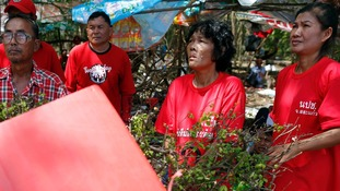 """Pro-government """"red shirt"""" supporters listen to their leader's speech inside their encampment in the suburbs of Bangkok today."""