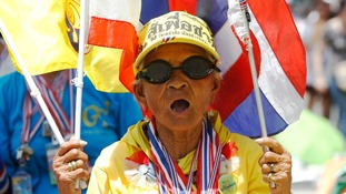 An anti-government protester holds Thai flags during a rally near the Government House in Bangkok today.