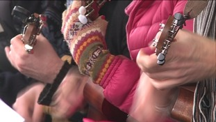 A close-up of three people's hands playing ukuleles