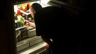 A man looks into his fridge full of food