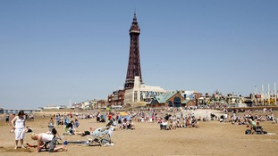 People enjoying the sunshine on the beach below Blackpool Tower