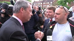 Farage clasps hands with a supporter during the visit.