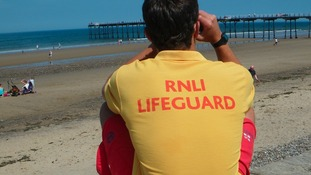 An RNLI lifeguard on the beach at Saltburn.