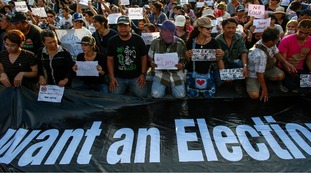 People hold signs while kneeling during a protest against military rule at Victory Monument in central Bangkok.