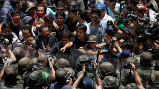 Protesters against military rule and soldiers deployed to control them confront each other at Bangkok's shopping district.