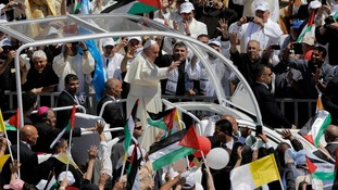Pope Francis waves to the crowd as he arrives to Manger Square in Bethlehem.