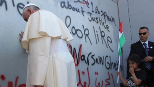 Pope Francis briefly prays at the Israeli separation barrier surrounding three sides of Bethlehem.
