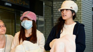 AKB48 members Rina Kawaei (L) and Anna Iriyama speak to media after being discharged.
