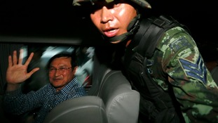 Chaturon Chaisang waves from inside a military van after being detained.