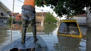 man navigates a boat along a street during heavy floods in Bosnia last week.