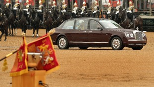 Queen Elizabeth II drives past members of the Household Cavalry before she presents them with new standards at Horse Guards Parade, London